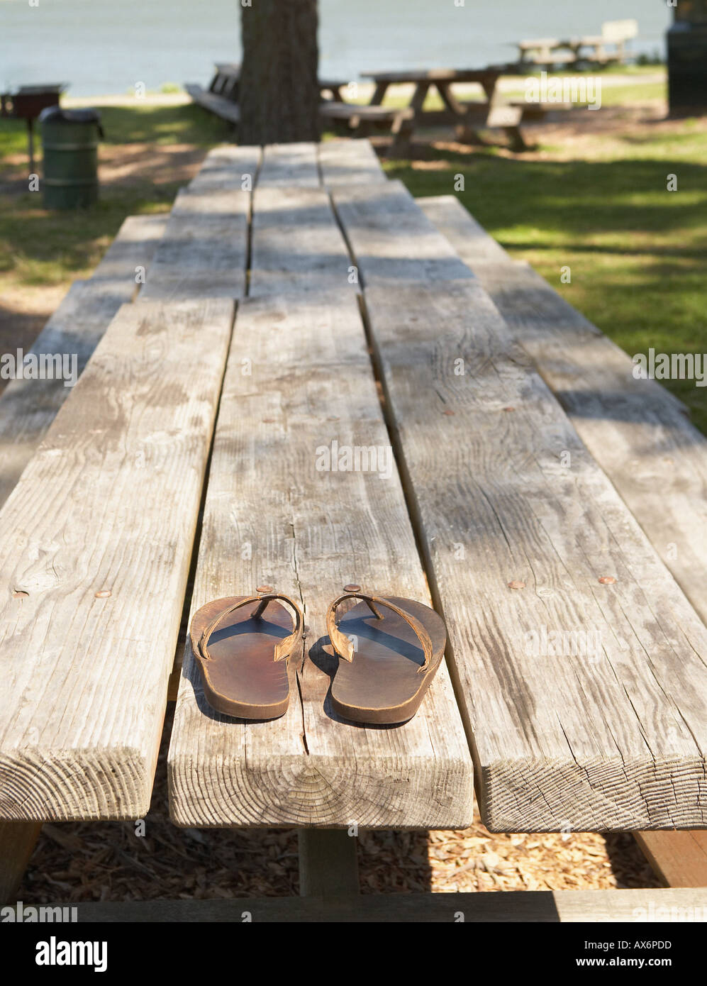 Sandals on a picnic bench - Stock Image