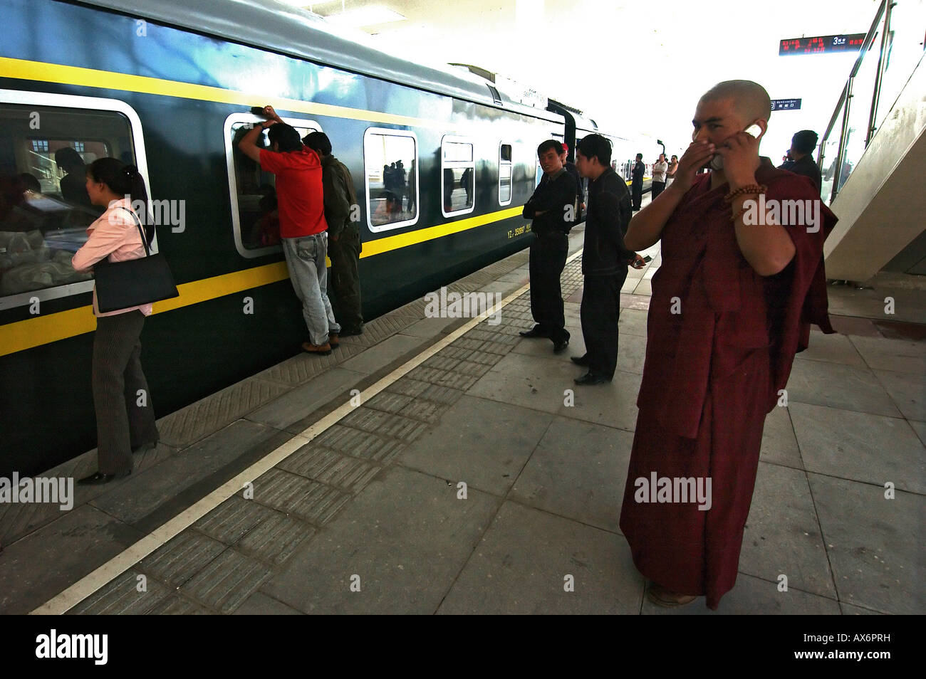 A monk speaks on a mobile phone as he waits to board a train departing from Lhasa train station. Tibet train - Stock Image