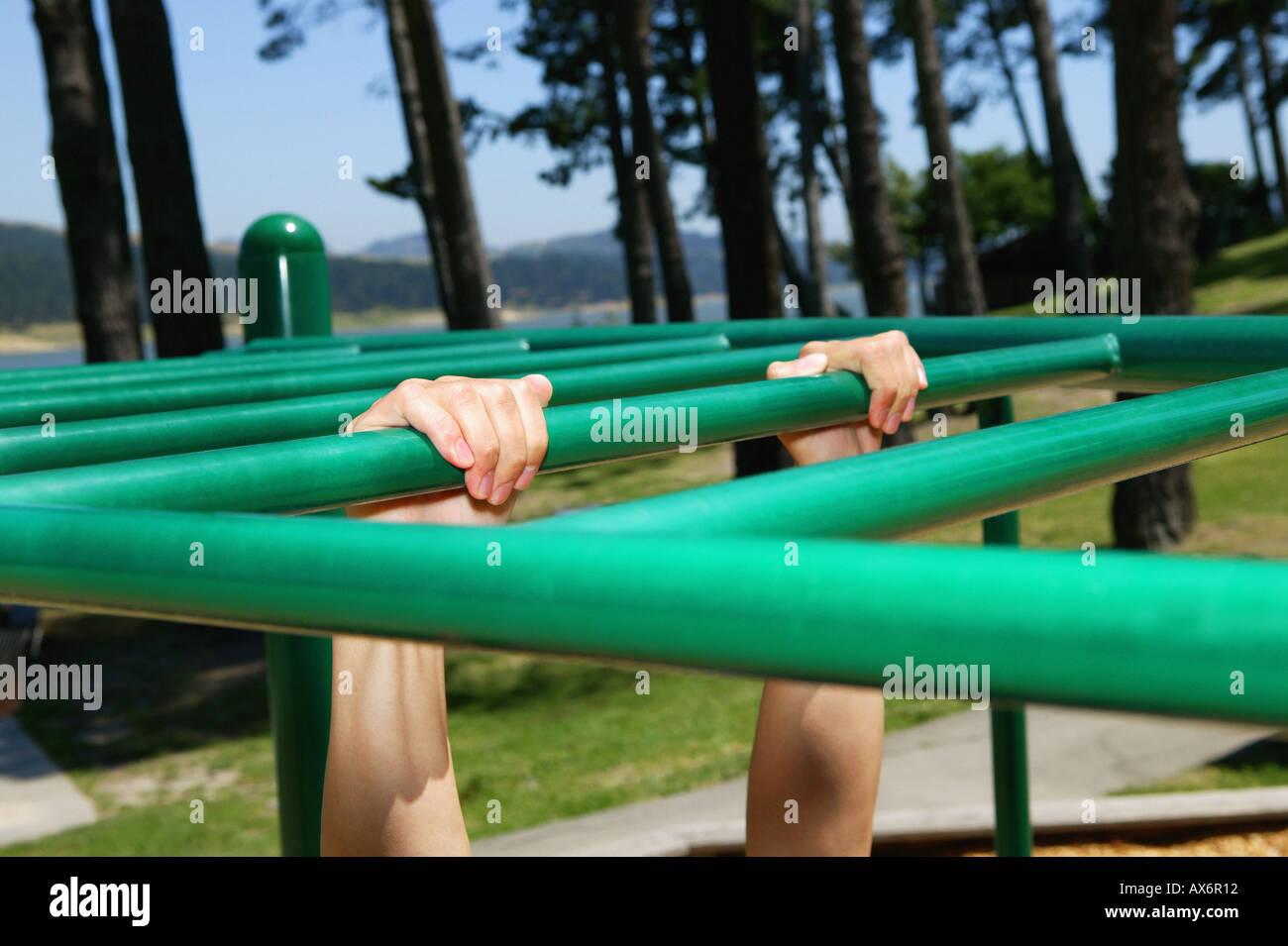 Person hanging onto monkey bars - Stock Image