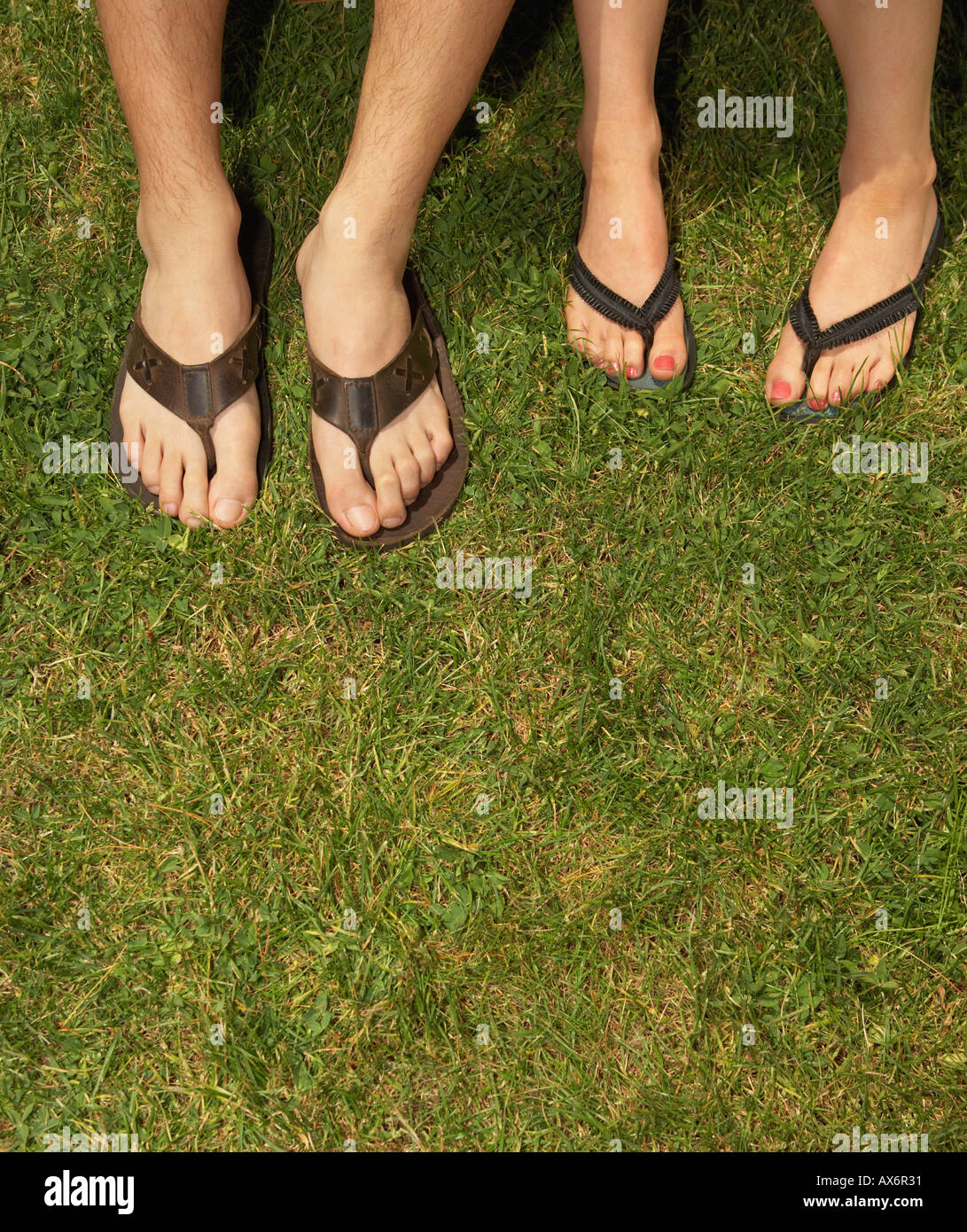 Male and female feet in sandals - Stock Image