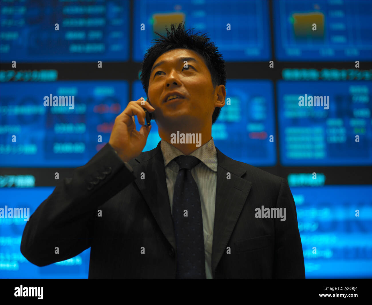 A Businessman talks on his mobile phone inside the electronic Tokyo Stock Exchange Tokyo Japan Released - Stock Image