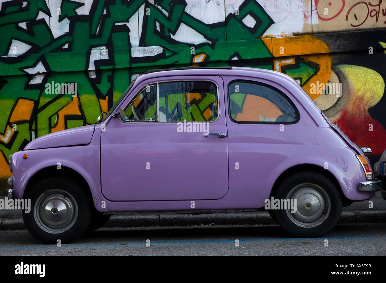 Italian old small car Fiat 500 with graffiti on the background Urban ...