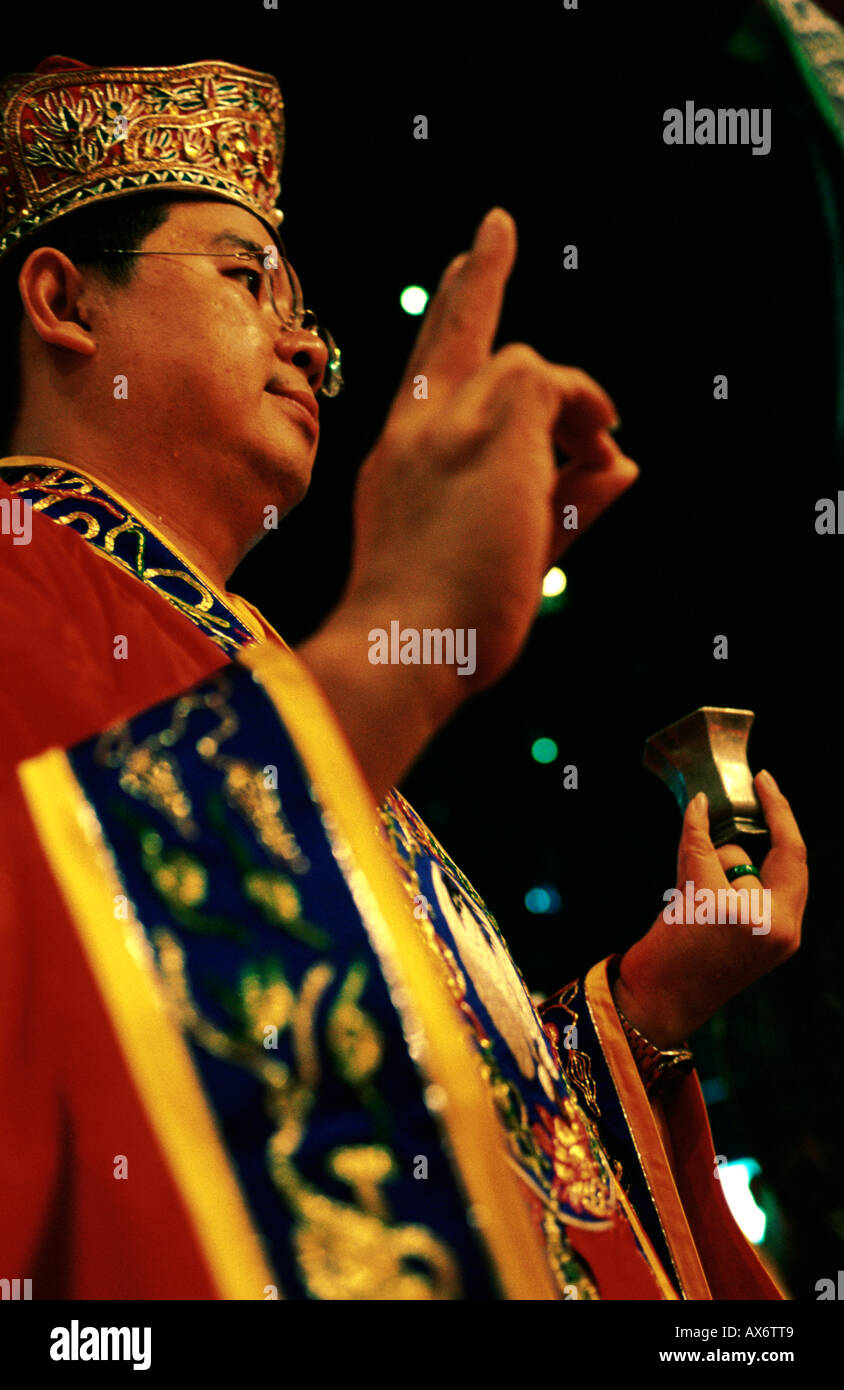 A buddhist priest makes a Mudra with his hand in a Chinese ceremony where he blesses the crowd Hong Kong - Stock Image