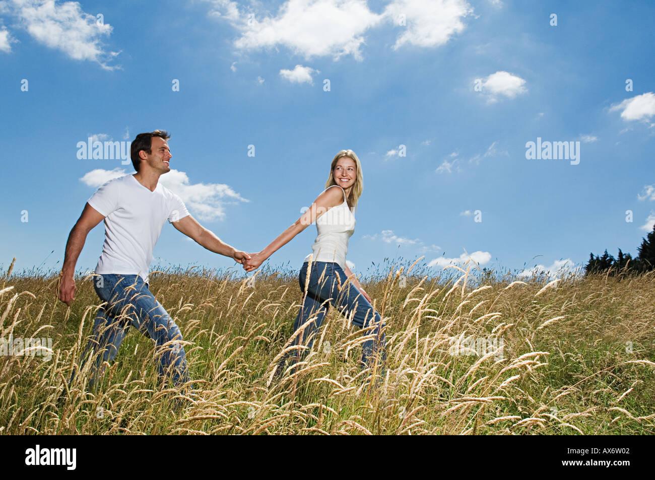 Couple walking in a field Stock Photo