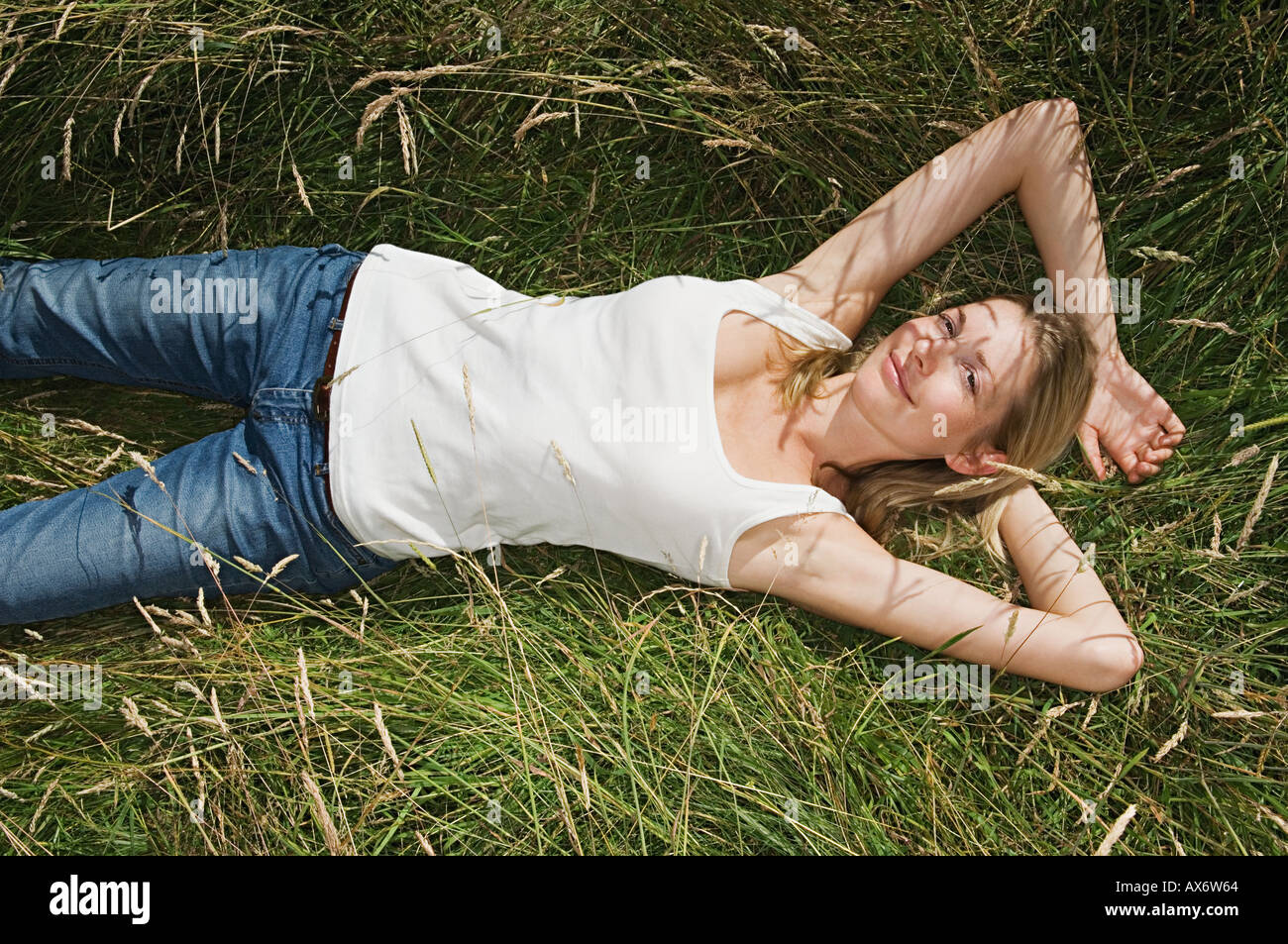 Woman lying in a field - Stock Image