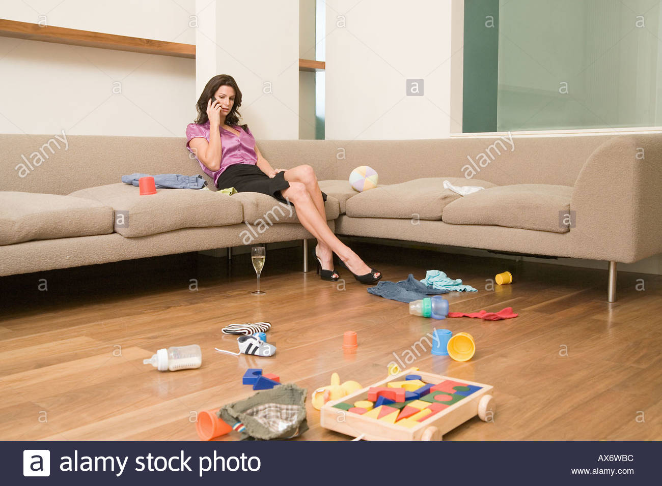 Mother on phone in messy room - Stock Image