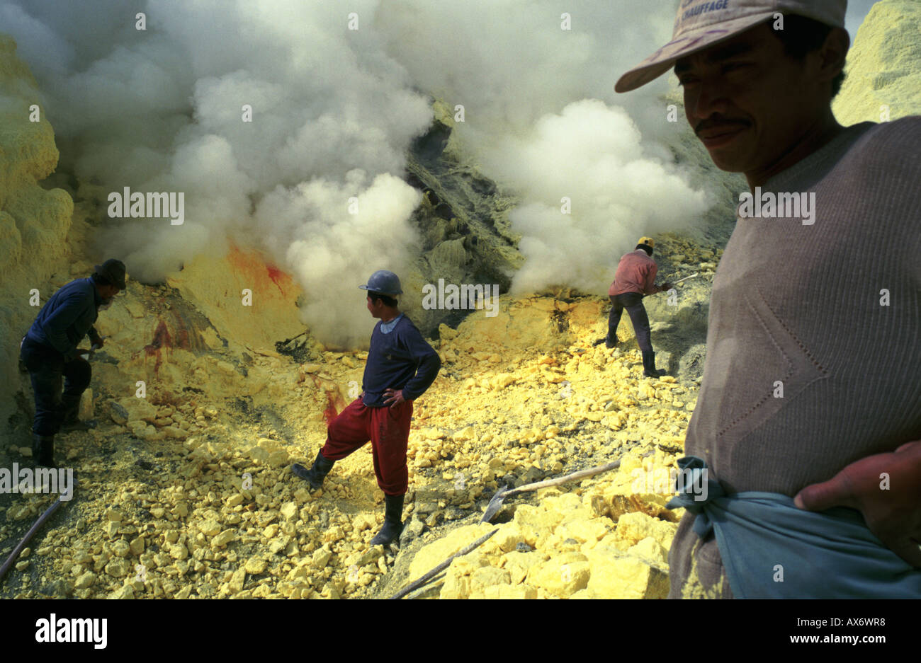 Men working inside the live volcano of Kawah Ijen in East Java Indonesia carry baskets of sulfur out of the volcanoe - Stock Image