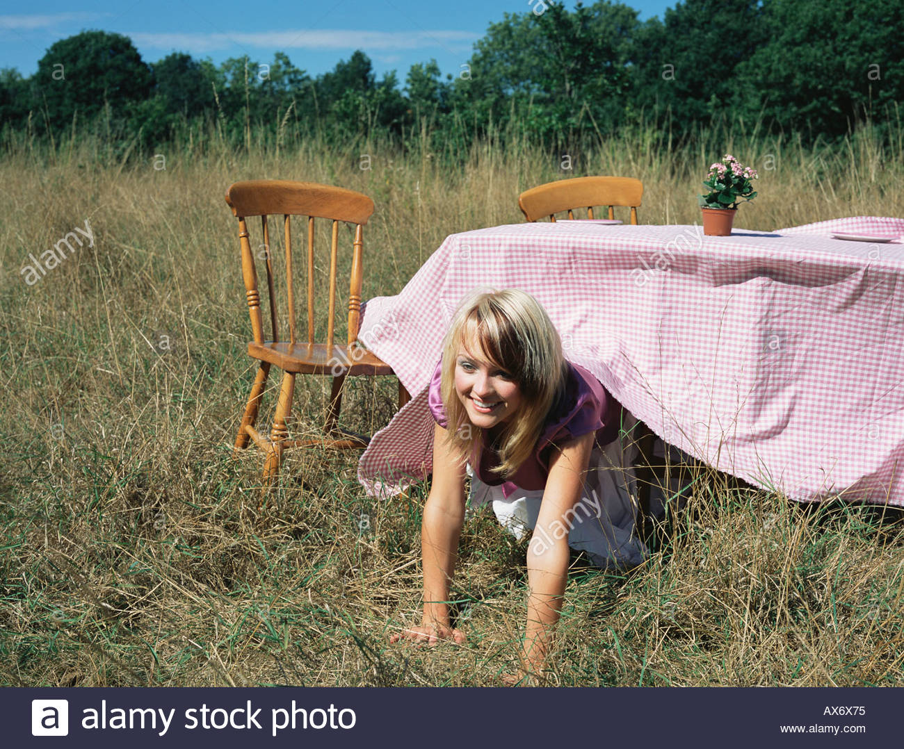 Young woman emerging from under a table - Stock Image