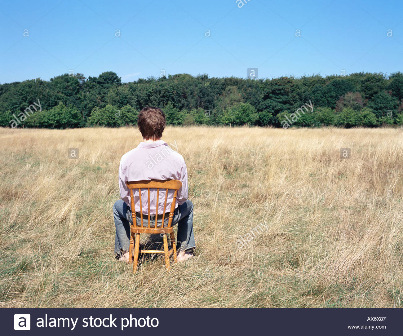 Man sitting on a chair in a field Stock Photo
