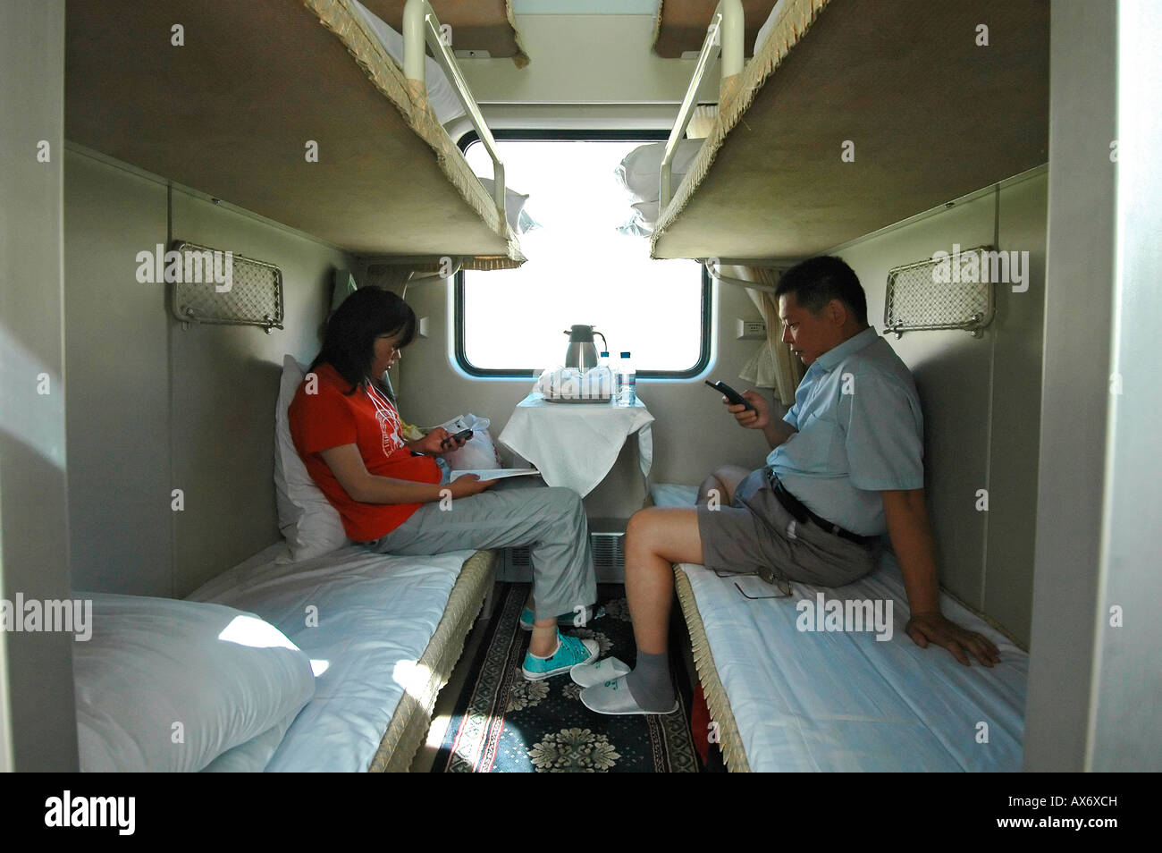 Passengers use mobile phones to send SMS messages from the Tibet train. Tibetan railway - Stock Image