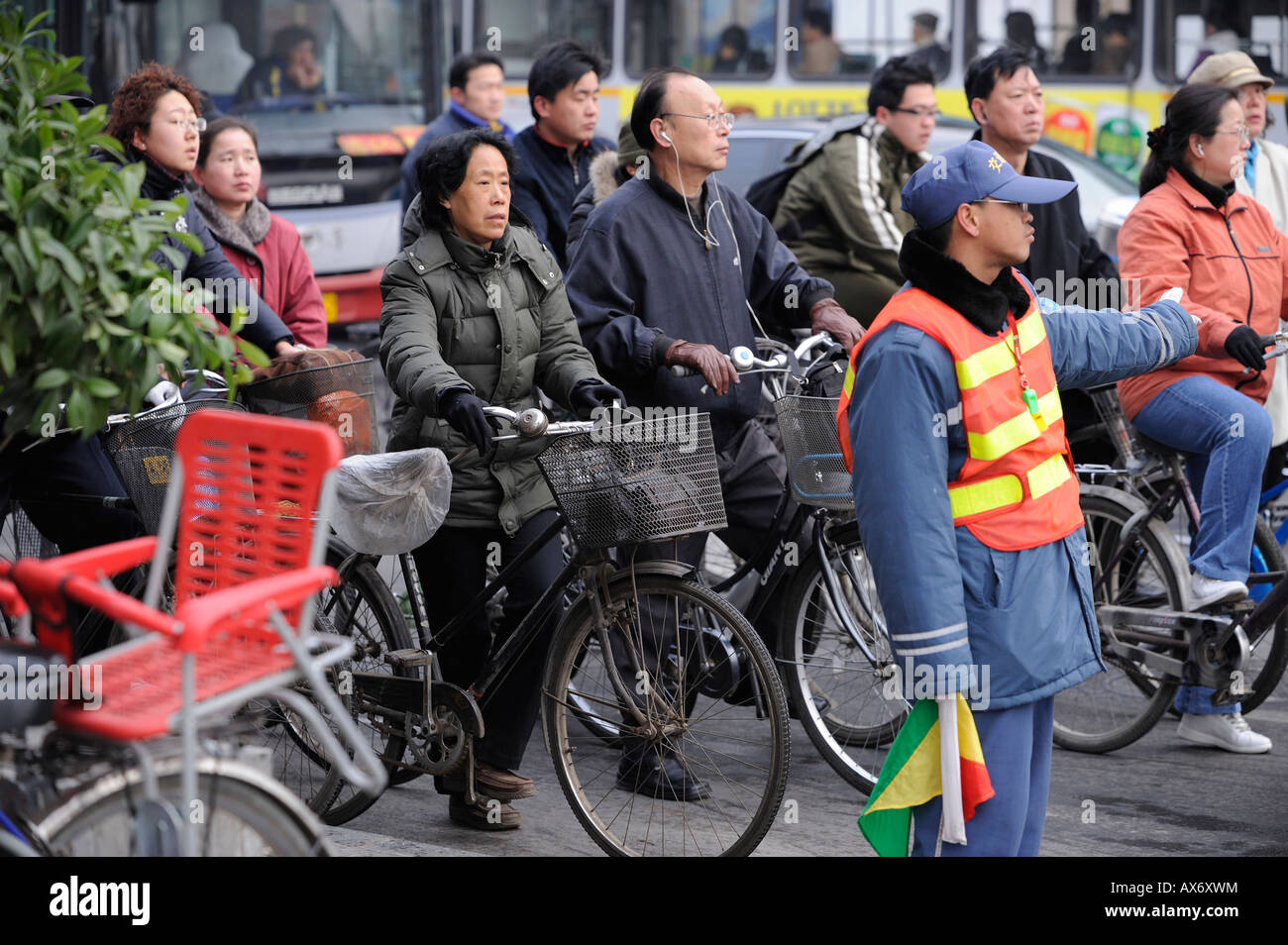 A man trying to keep cyclists following the traffic rule at a crossing in Beijing, China. 20-Mar-2008 - Stock Image