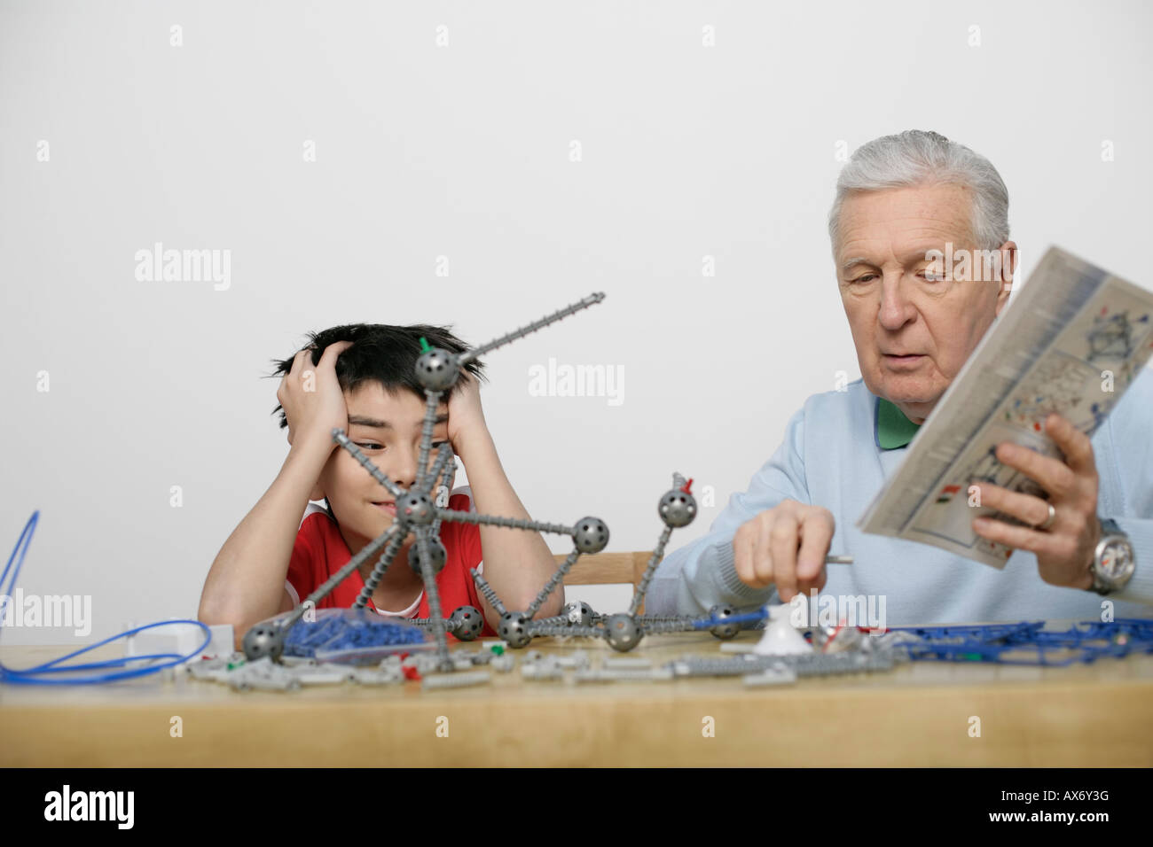 Grandfather and boy playing with a construction kit, fully_released - Stock Image