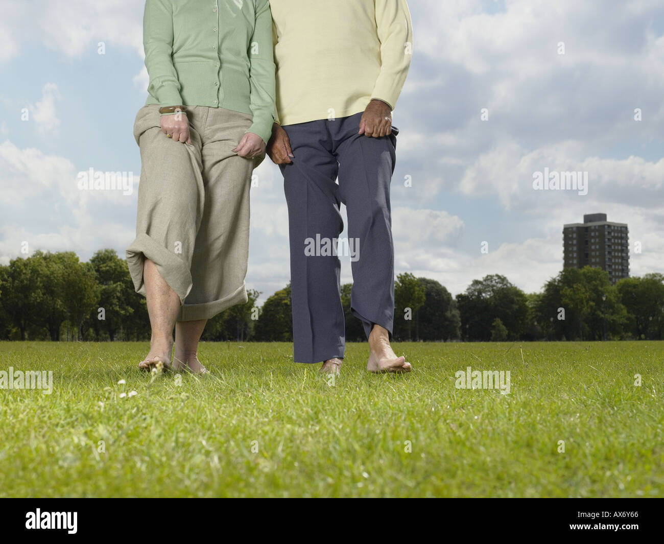 Elderly couple walking bare foot in the park - Stock Image
