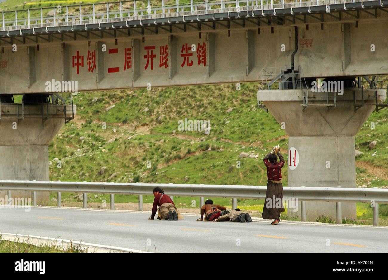 Nomad pilgrims prostrate before a railway bridge en route to Lhasa from Nagchu in northern Tibet. Tibetan train - Stock Image