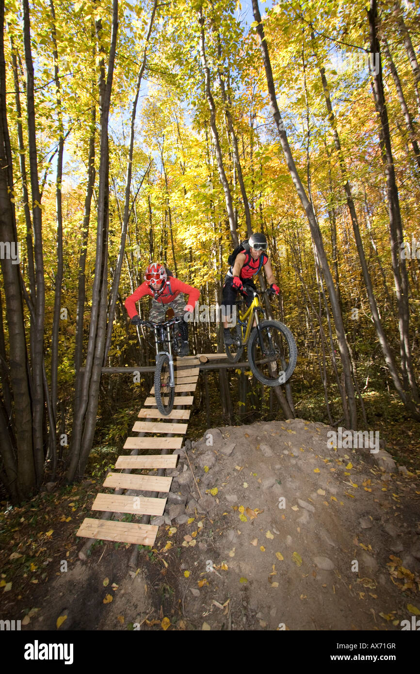 Italy, South Tyrol, Bozen, mountainbikers overcoming an obstacle - Stock Image