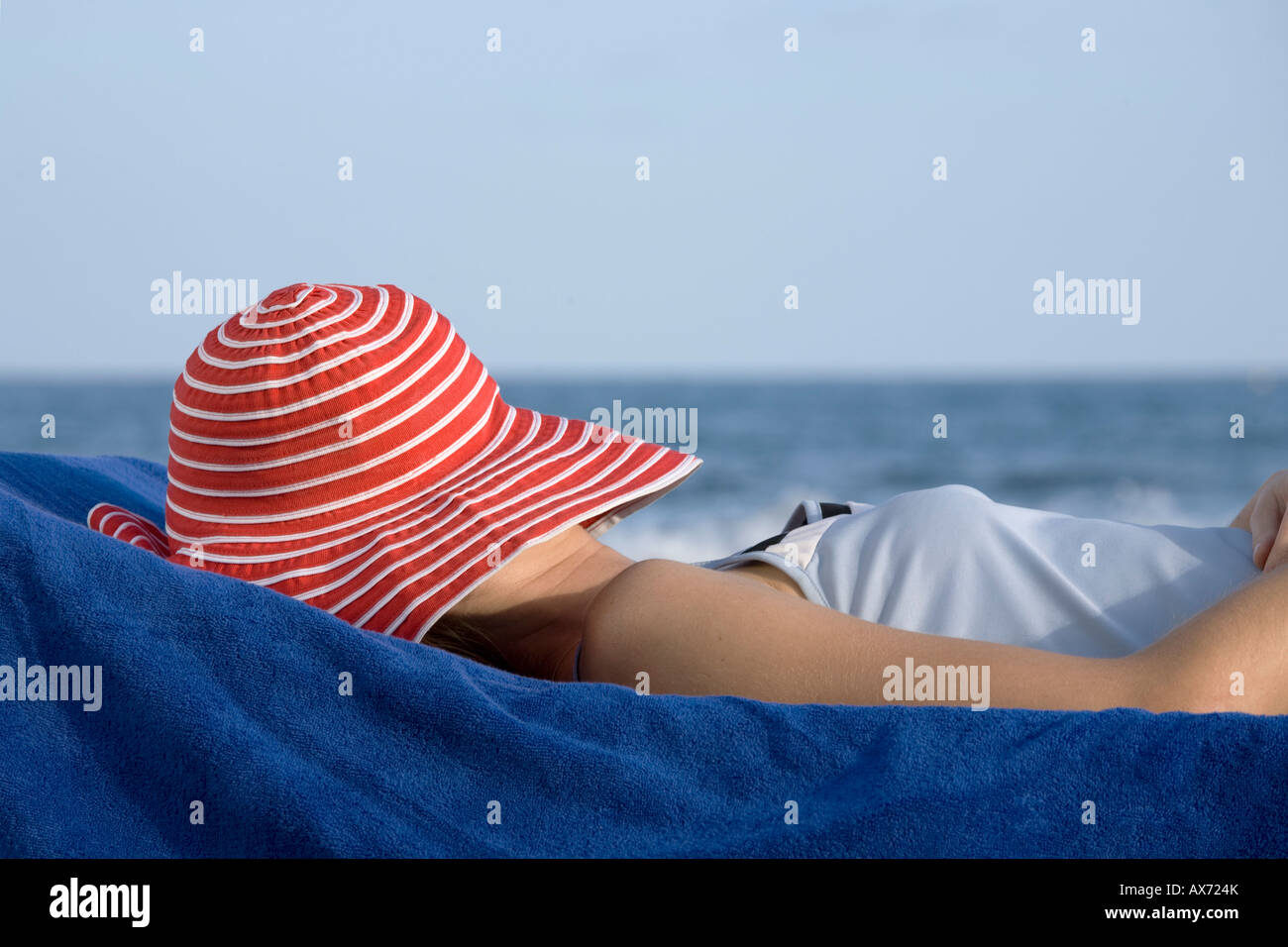 Woman with hat, lying on beach - Stock Image