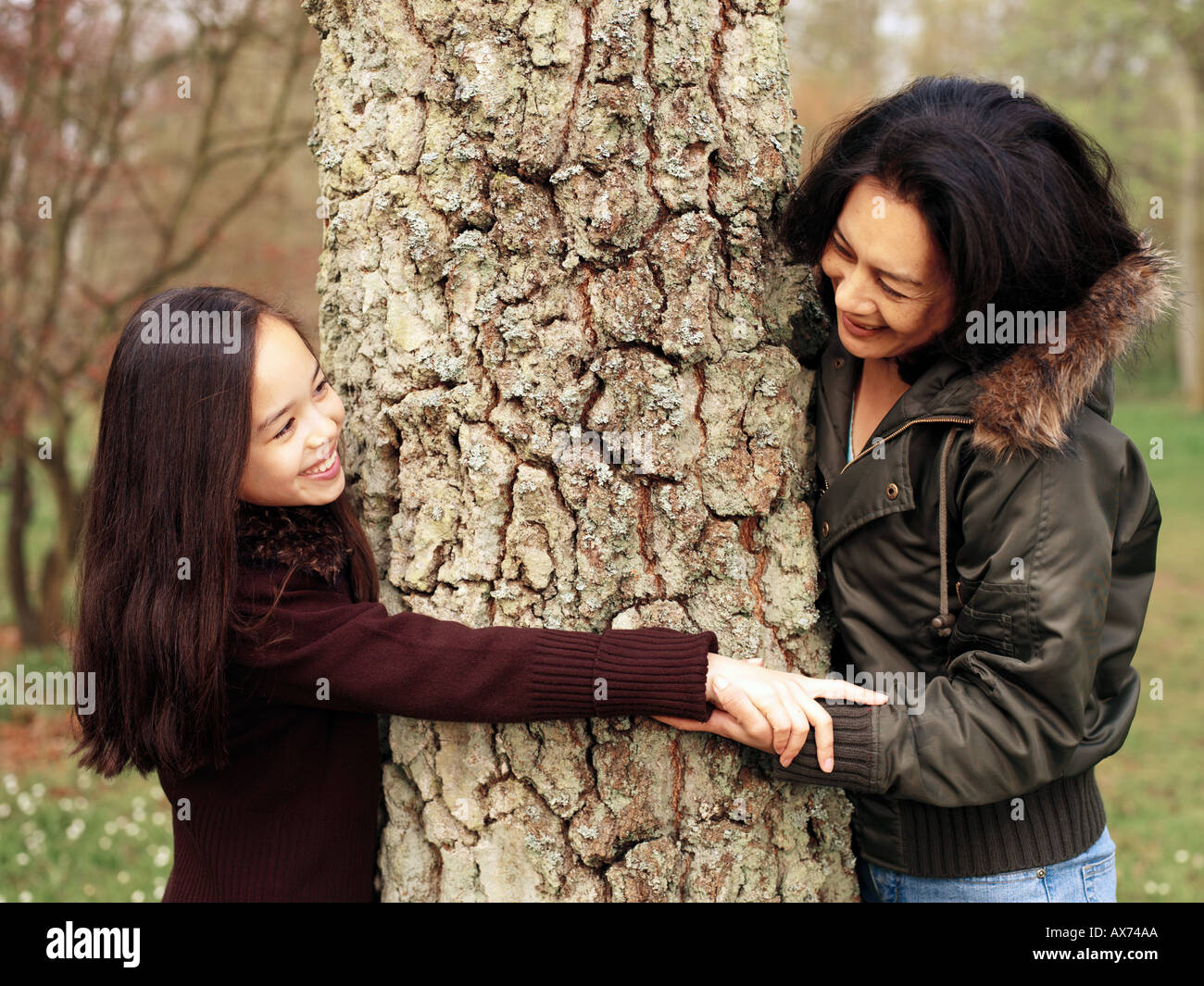 mother and daughter reaching around a tree - Stock Image