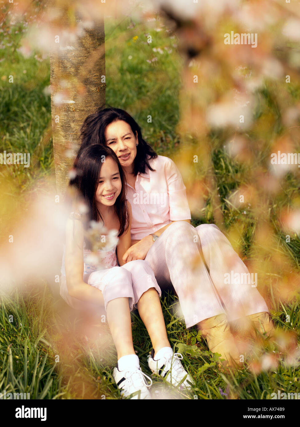 mother and daughter sat beneath cherry tree - Stock Image