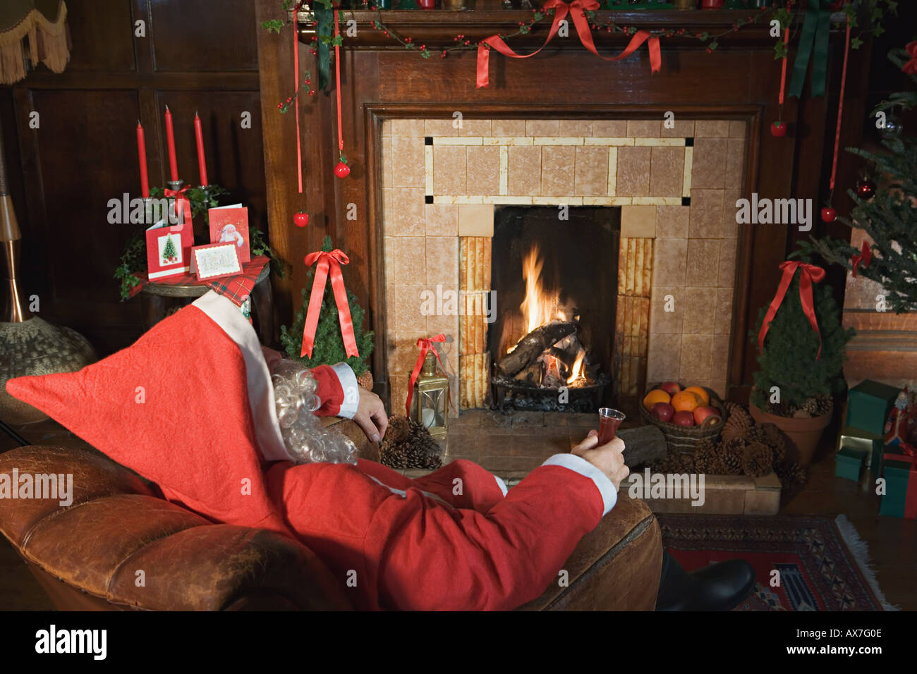Santa claus drinking sherry by the fire - Stock Image