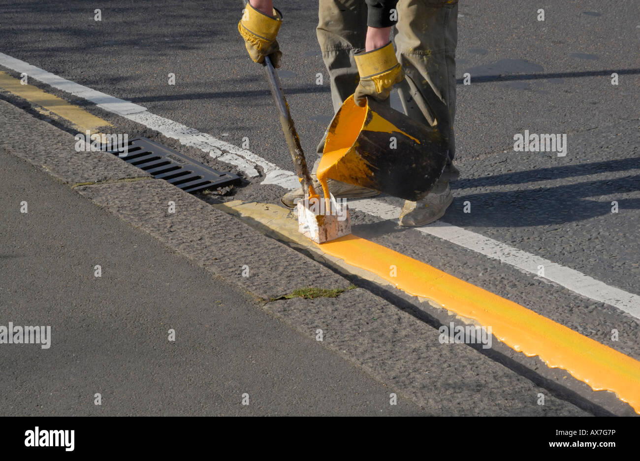 Hand painting yellow line on road with kettle of hot paint and marking tool, Cheam, south London, Surrey, EnglandStock Photo