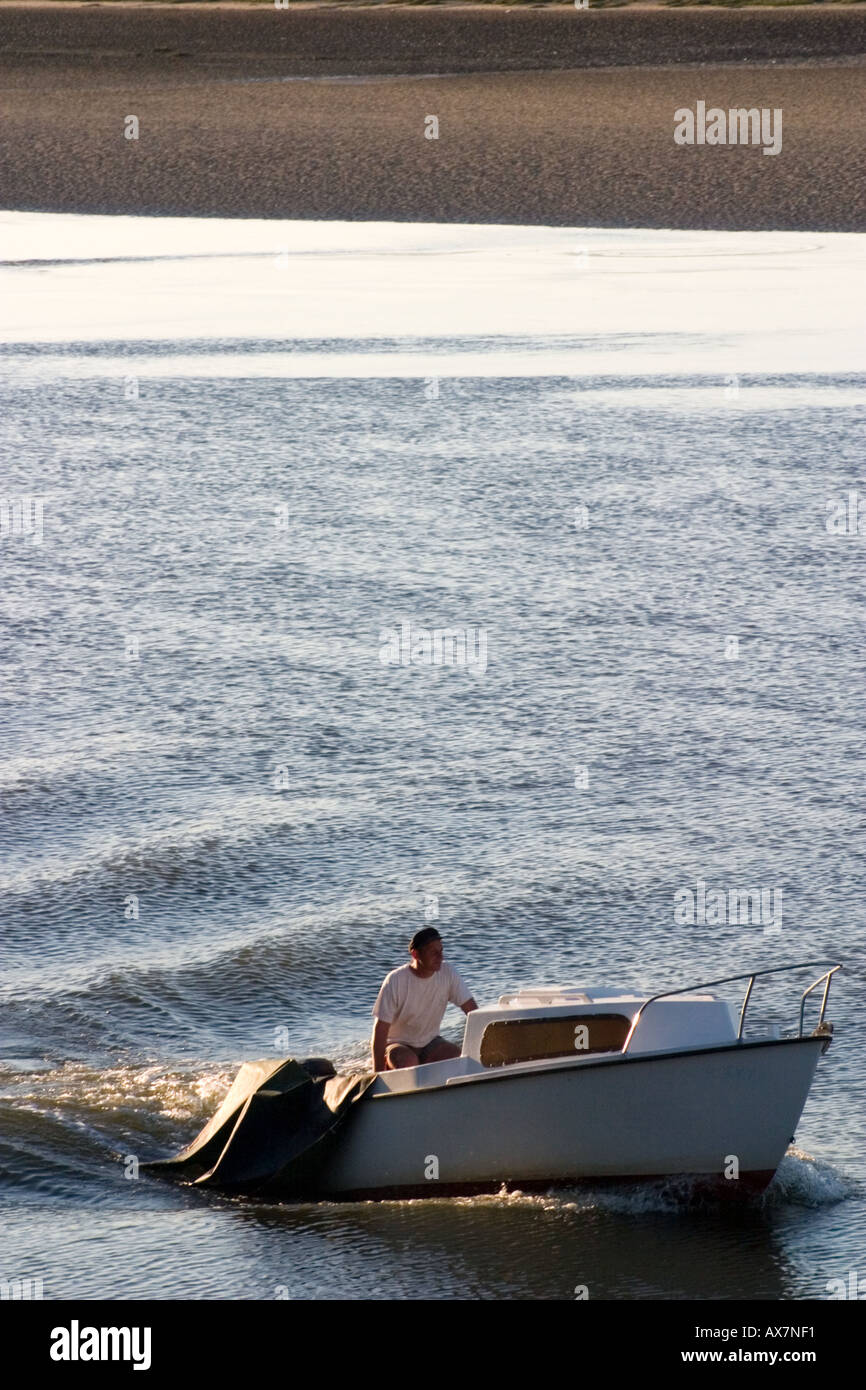 Lone fisherman in small cabin cruiser returns to port in