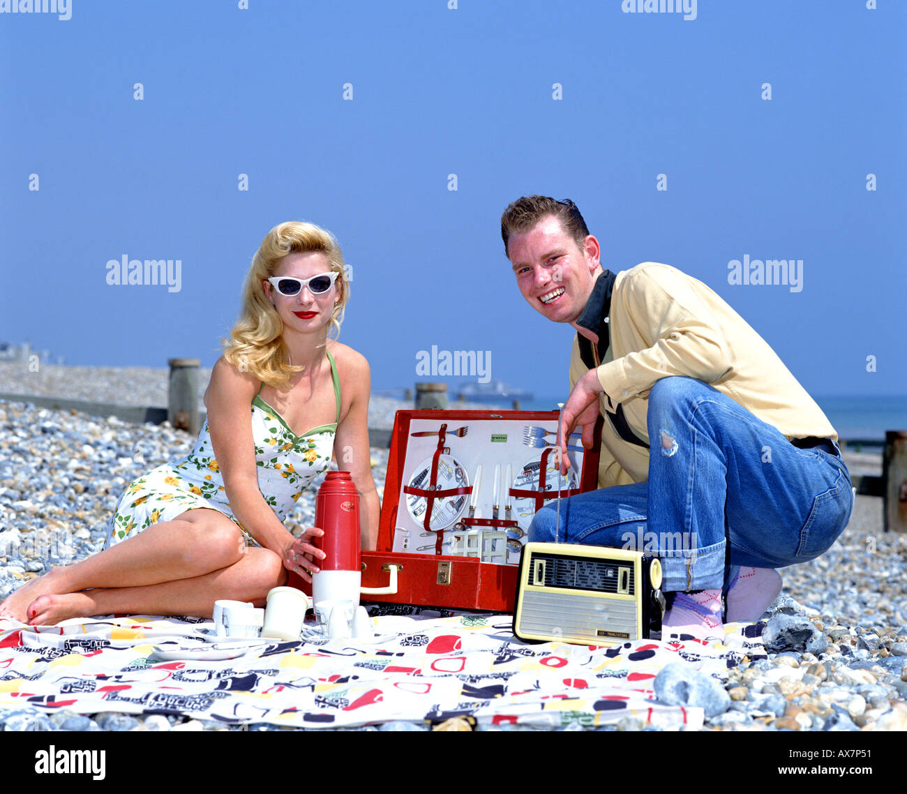 50s Style Couple sitting on the beach with picnic hamper - Stock Image