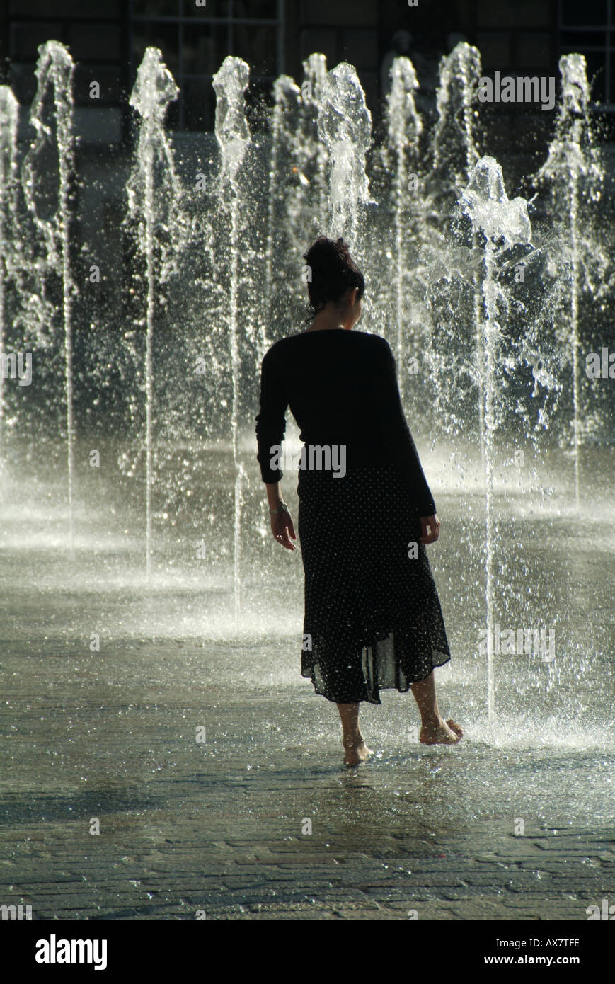 Fountain water feature young woman cooling off hot summer weather concept testing the water or dipping toe in water London England UK - Stock Image
