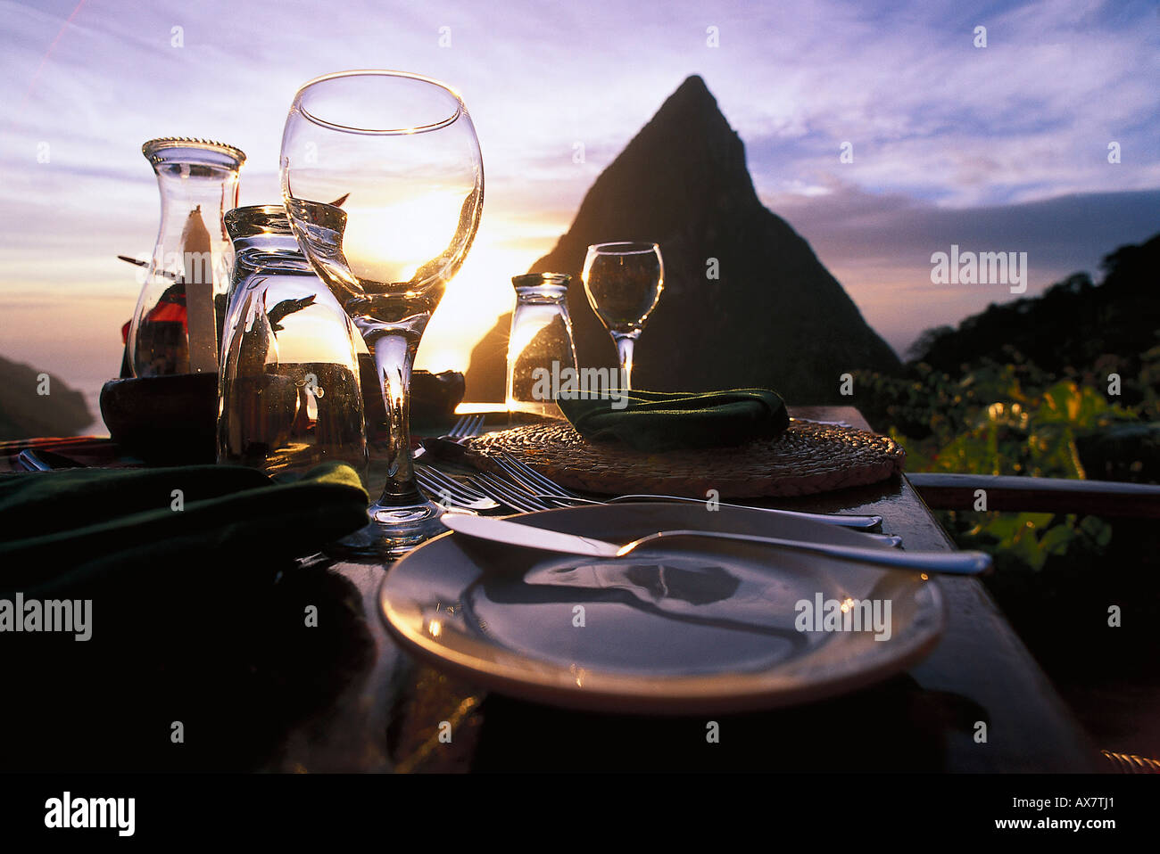 A table is laid on the terrace of the Restaurant Dasheene at sunset, Soufriere, St. Lucia, Carribean - Stock Image