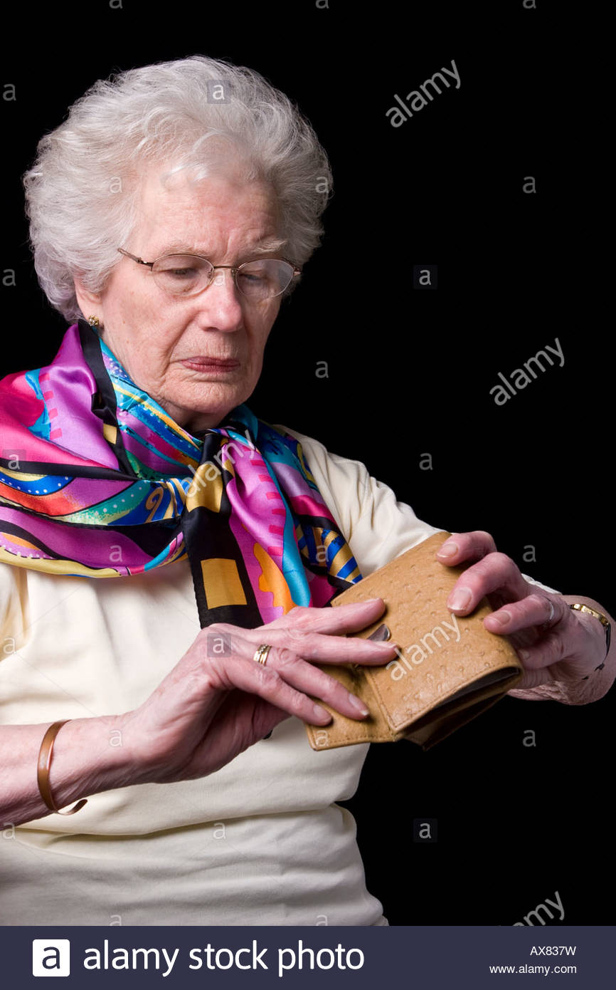 An old woman turning out an empty purse. - Stock Image