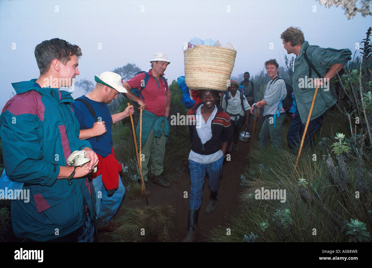 Bergsteiger und Traeger, Moorzone, Marangu Route, Kilimanjaro Tansania Stock Photo