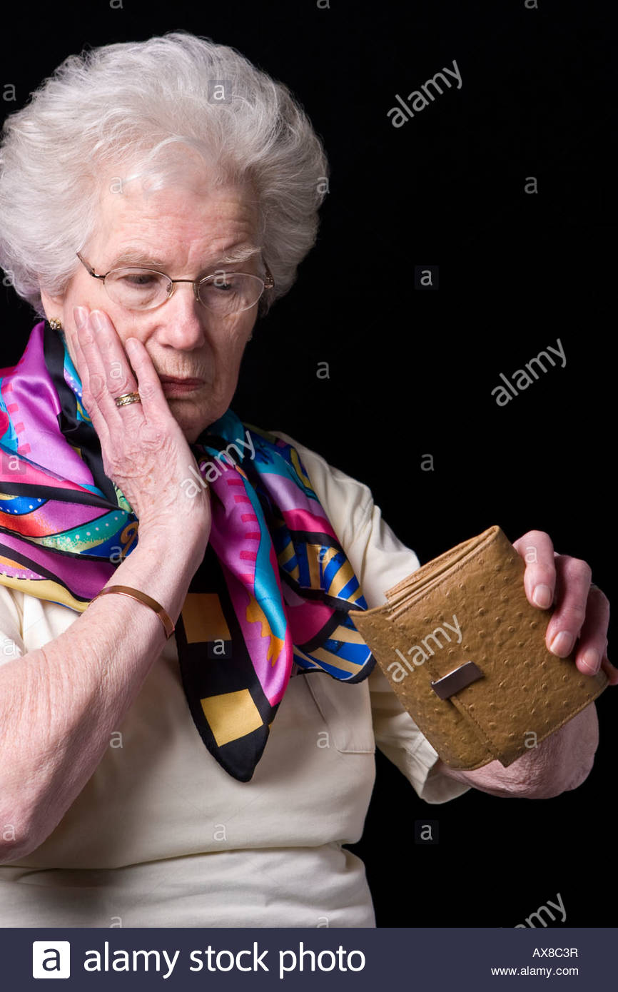 An old woman shocked to find her purse is empty. - Stock Image