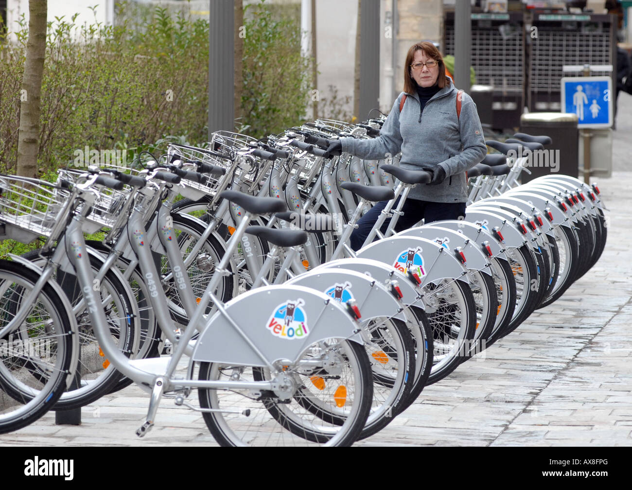A woman hiring a bicycle in Dijon, Burgundy, France. - Stock Image