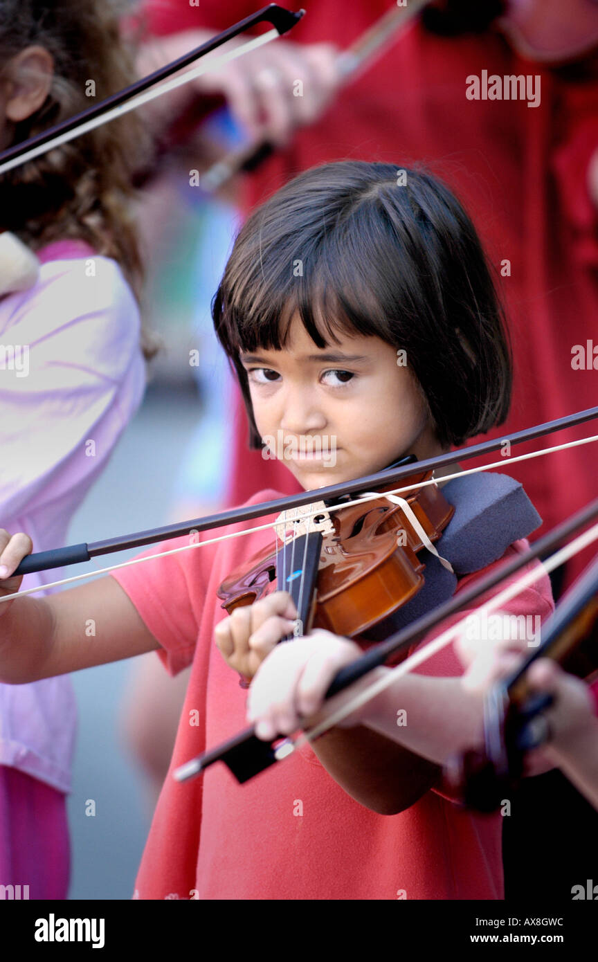 Violin strings group made up of children play a recital outside for the public - Stock Image