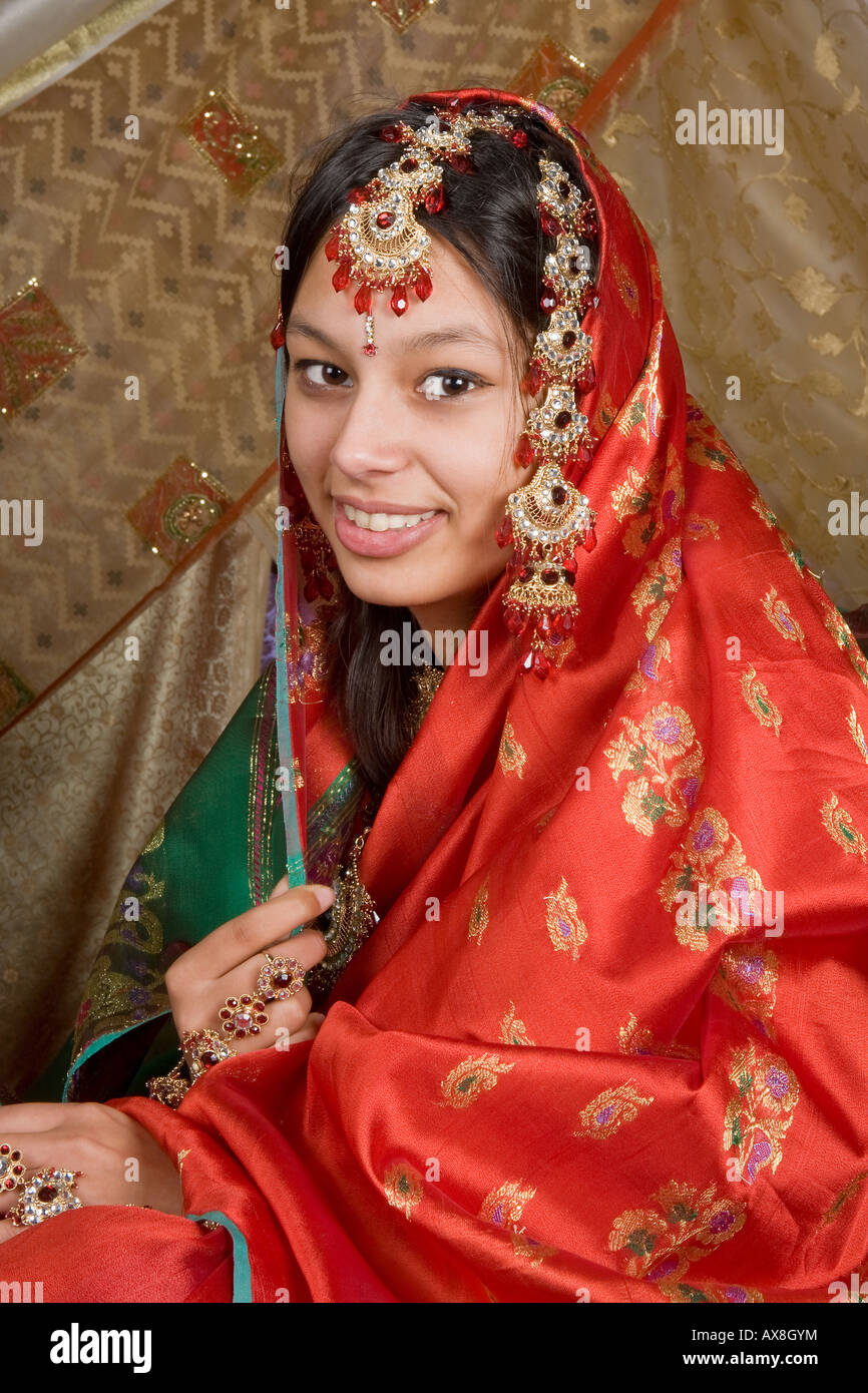 Young Exotic Indian Woman Wearing A Red Saree And Bridal Jewelry