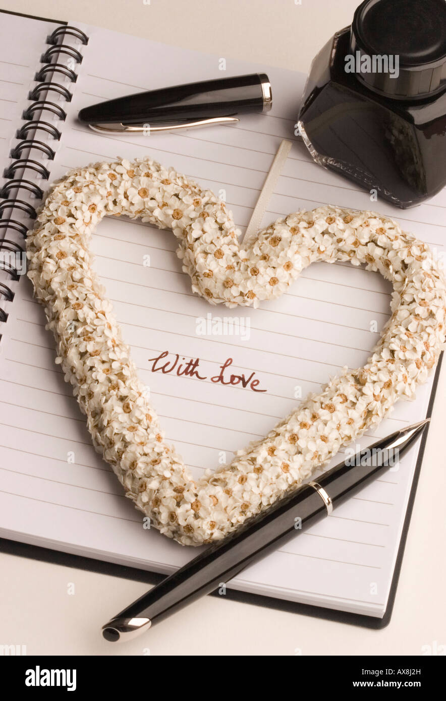 The words 'with love' hand written by an ink fountain pen within a heart shape made of flowers - Stock Image