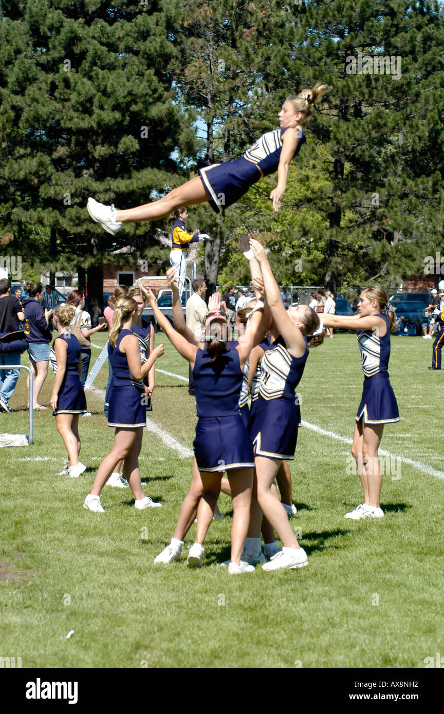 Female Cheerleaders Perform During Football Game doing routine that risks injury - Stock Image