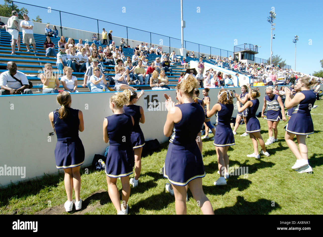 Cheerleaders Perform During Football Game doing routine that risk injury - Stock Image