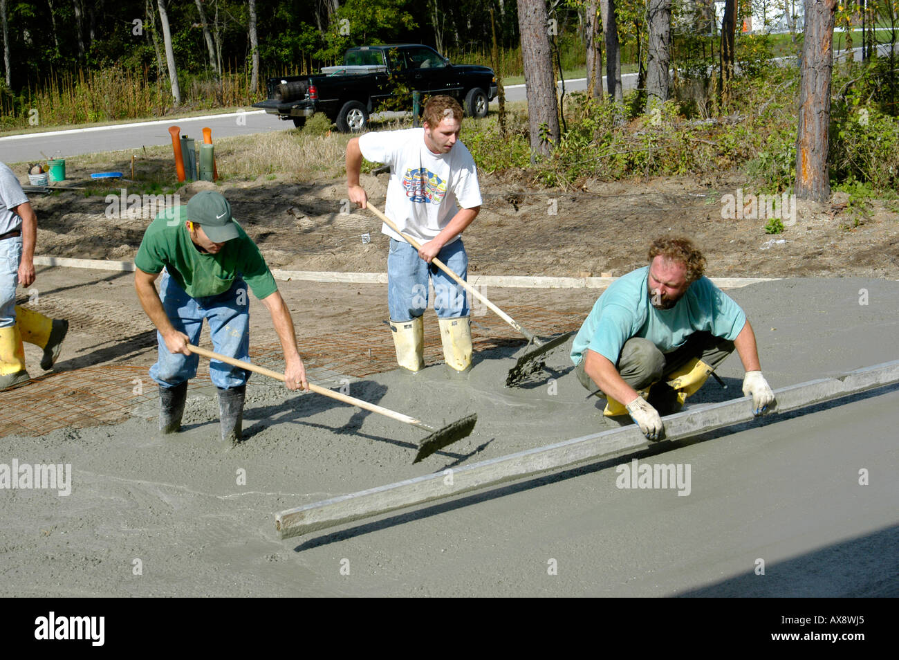 Cement Mason workers pour and finish a concrete driveway in