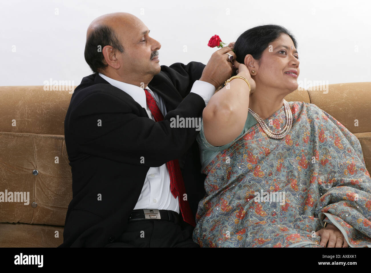 Senior man tucking rose in the hair of his wife - Stock Image