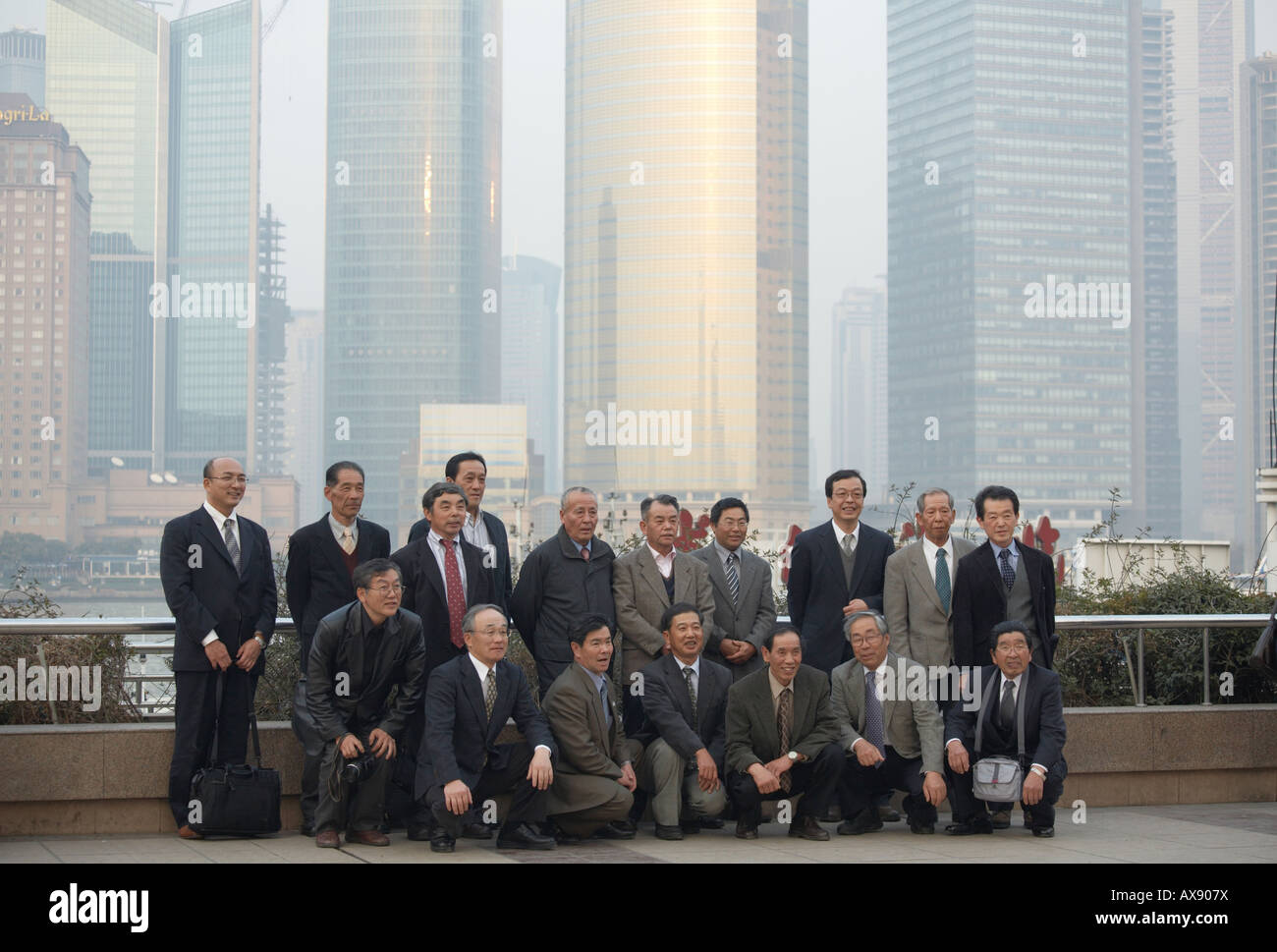 Japanese businessmen posing for a group photo on the Bund with Pudong business district in the background in Shanghai - Stock Image