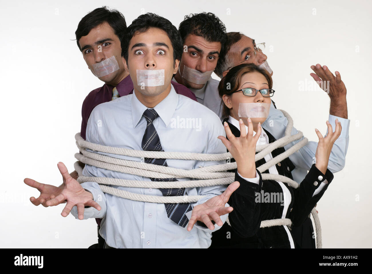 Portrait of five business people tied up with ropes - Stock Image