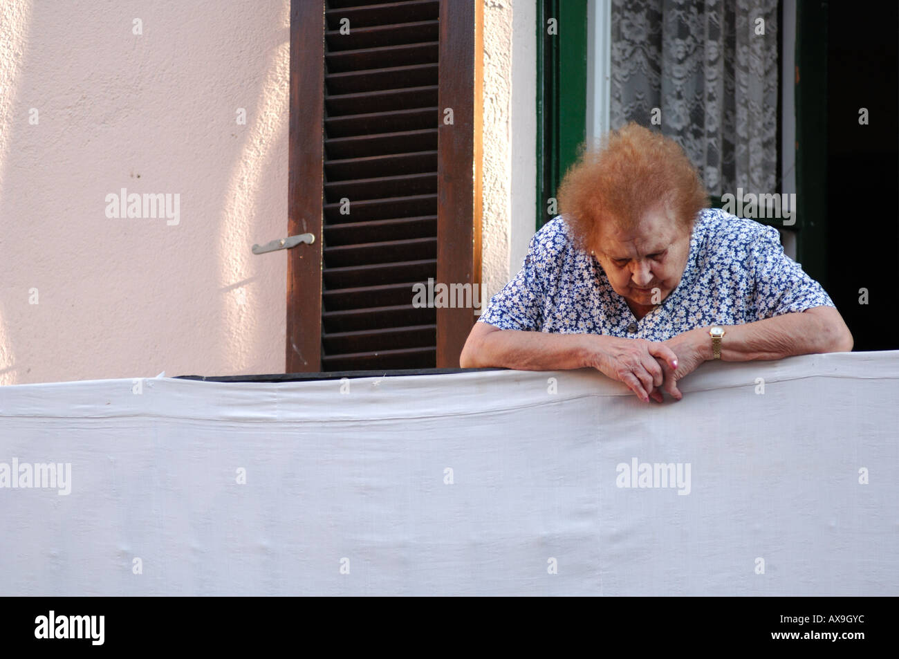 elderly lady watching the world go by from balcony in castello d empuries catalonia spain Stock Photo