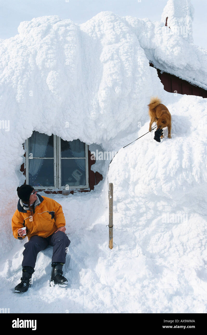 Man and dog in front of a snowed in mountain hut, Areskutan, Are, Sweden - Stock Image