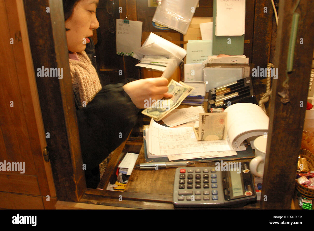 A cashier at Tsukiji fish market. - Stock Image
