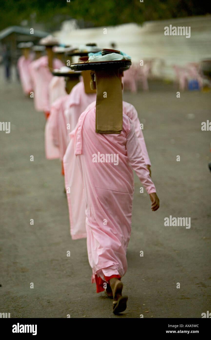 Line of nuns in pink robes, Reihe Nonnen in rosa Gewand gehen Almosen sammeln - Stock Image
