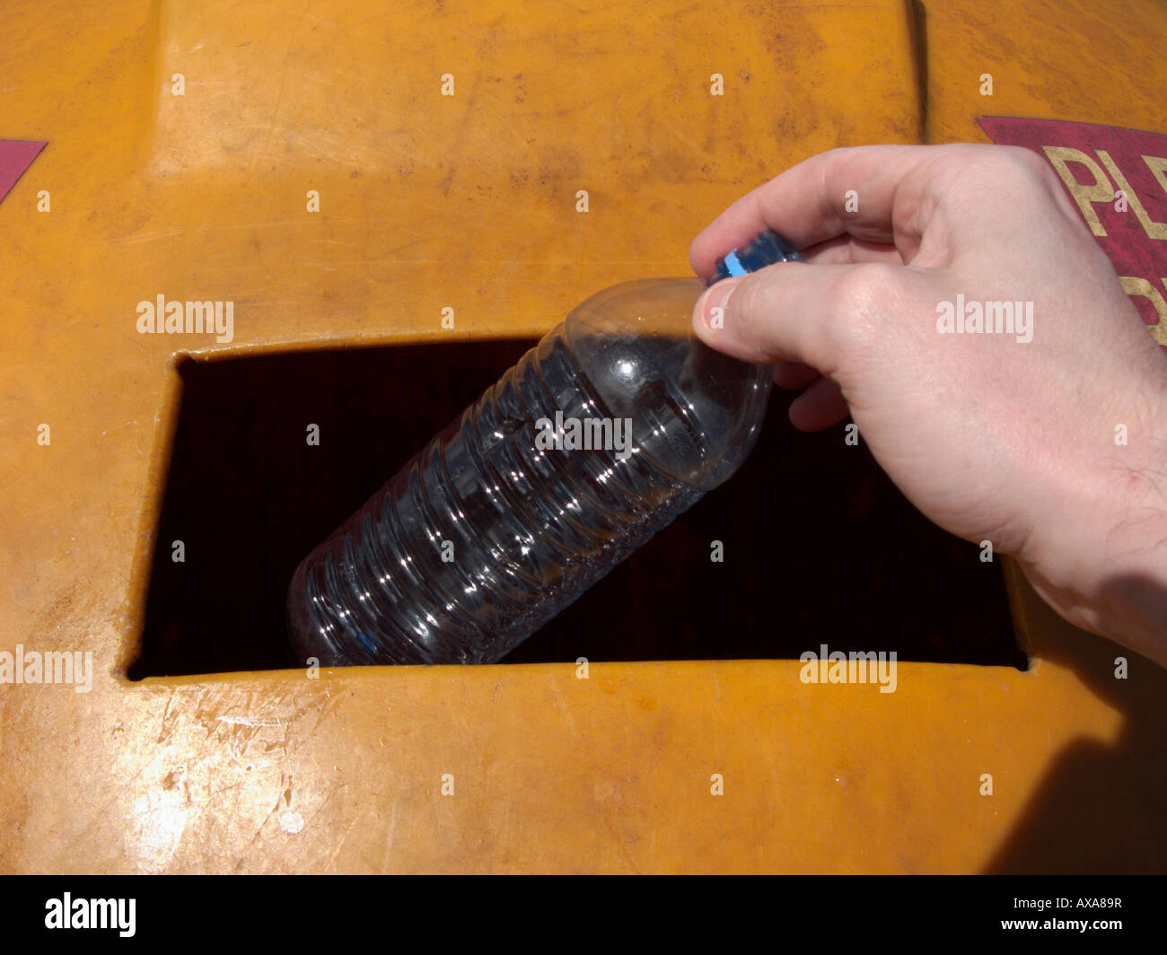 mans hand placing a recyclable empty clean plastic bottle in a recycling bin at recycling depot Stock Photo