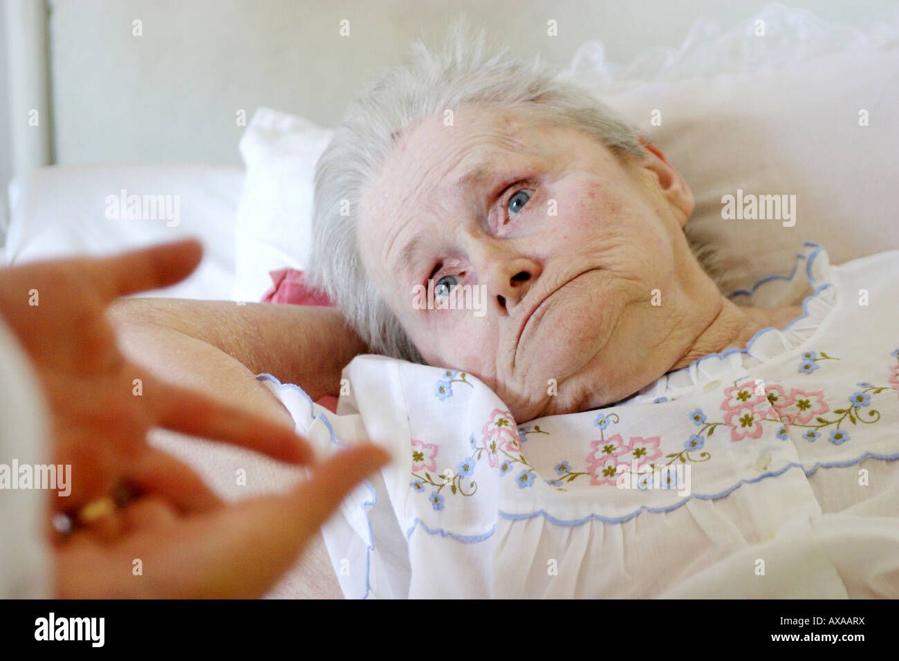 A nurse talking with an elderly woman lying in bed, Poland - Stock Image