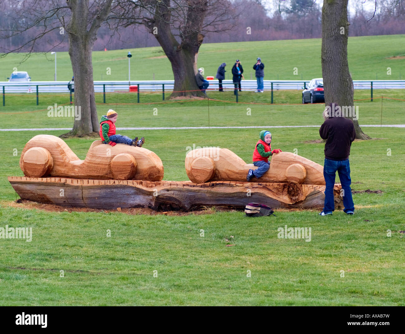 Young Children Playing on Wooden Racing Car Sculpture Carved From Fallen Tree at Oulton Park Motor Race Track Cheshire Stock Photo