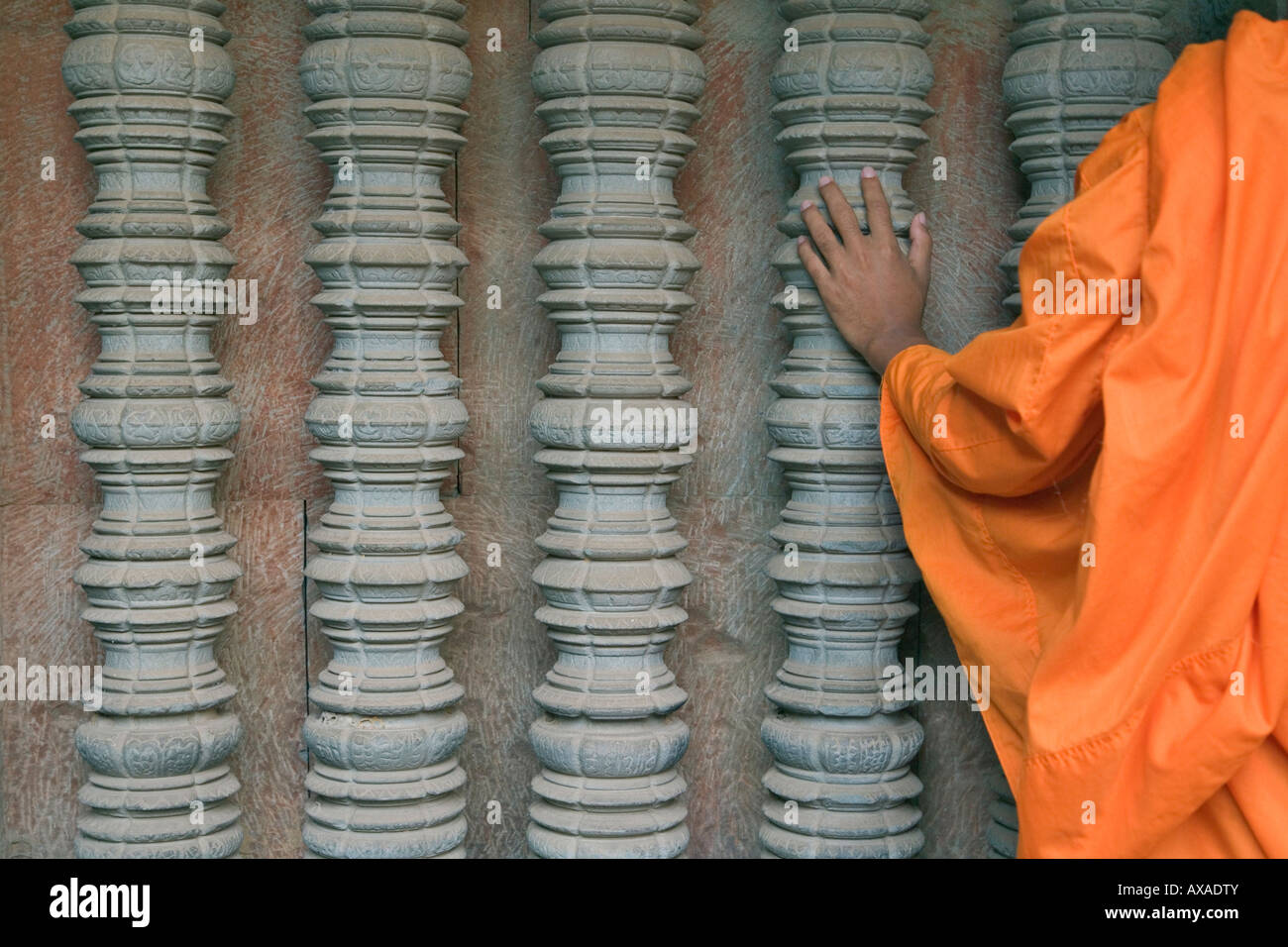 Monk with detailed carving in Angkor Wat Cambodia - Stock Image