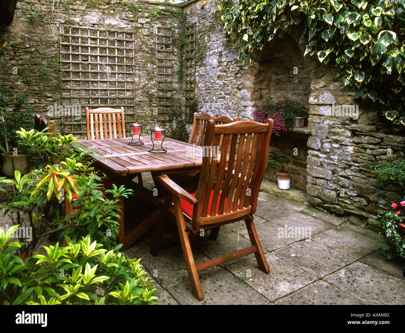 Small garden patio, walls around, wooden tables and chairs Stock ...